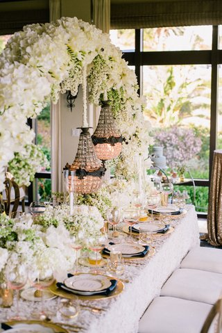 wedding-reception-table-with-white-floral-arch-and-suspended-glass-beaded-chandeliers