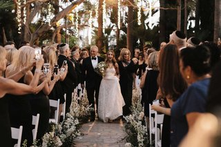 bride-walking-down-aisle-with-mother-and-father-beverly-hills-outdoor-ceremony-string-lights