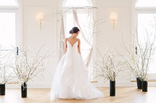 bride-in-hayley-paige-wedding-dress-layered-skirt-plunging-neckline-spaghetti-straps