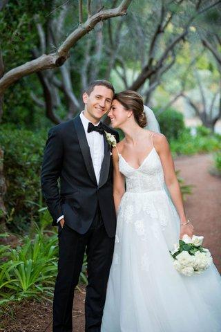 bride-in-spaghetti-strap-monique-lhuillier-wedding-dress-lace-flower-design-groom-in-tuxedo-bow-tie