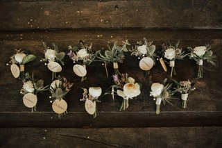 two-row-of-boutonnieres-made-with-sea-holly-and-ivory-blooms