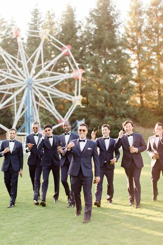 groom-and-groomsmen-in-midnight-blue-tuxedos-in-front-of-ferris-wheel-with-flask-and-cigars