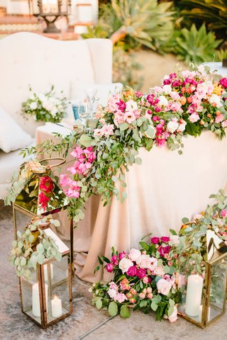 sweetheart-table-with-blush-linen-pink-orange-flowers-greenery-gold-lanterns-white-settee-for-couple