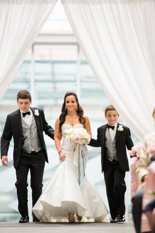 bride-white-trumpet-dress-walked-down-the-ceremony-aisle-by-her-tow-young-sons-in-black-tuxedos