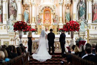 wedding-ceremony-catholic-church-red-rose-arrangement-on-both-sides-of-altar-bride-in-gown