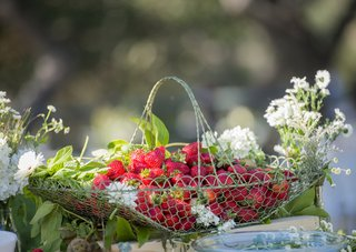 basket-of-red-strawberries-with-green-leaves-and-white-wildflowers-on-table