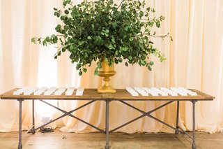 bare-wood-table-industrial-with-gold-urn-filled-with-green-leaves-white-escort-cards-on-top