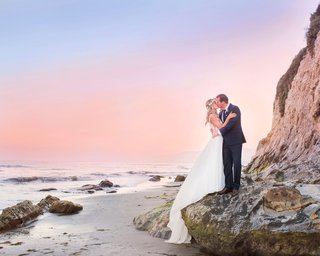 wedding-portrait-sunset-photo-of-bride-and-groom-flower-crown-santa-barbara-beach-cotton-candy-skies