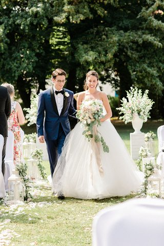 bride-and-groom-walking-down-aisle-together-navy-blue-tuxedo-white-bridal-gown-aisle-flower-petals