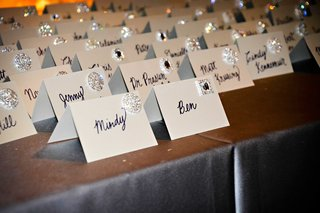 silver-buttons-on-white-tent-place-cards-with-hand-written-names-in-cursive