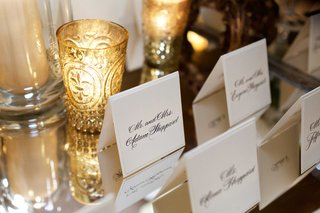 black-and-white-tent-escort-cards-on-mirrored-table-net-to-gold-candle-votives-and-hurricanes