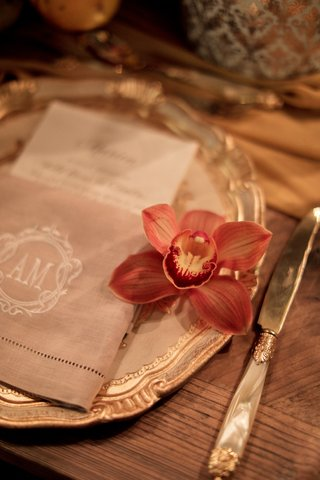 blood-orange-orchid-on-the-side-of-napkin-and-menu-on-charger-plate