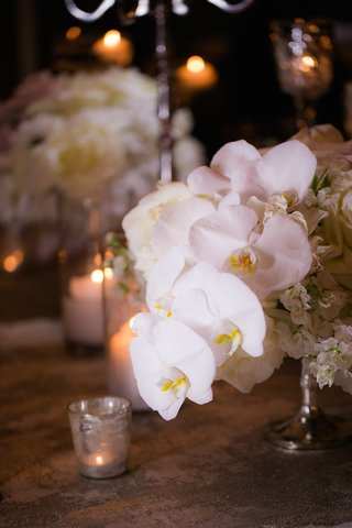 wedding-reception-table-with-white-orchids-hydrangeas-in-a-silver-stand
