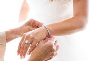 mother-of-the-bride-puts-diamond-tennis-bracelet-on-bride