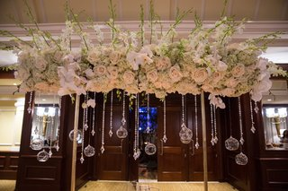 wedding-reception-table-with-golden-structure-topped-with-light-roses-white-orchids-mint-hydrangea