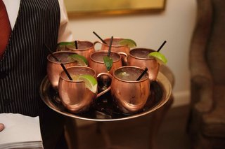 copper-moscow-mule-mugs-on-tray-with-lime-and-black-straws