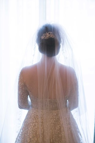 bride-showing-off-back-dress-veil-headpiece-elegant-up-do-twigs-and-honey-roman-catholic-wedding