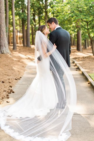 couple-portrait-in-wooded-area-forest-camp-with-sheer-veil-and-lace-trim-hem