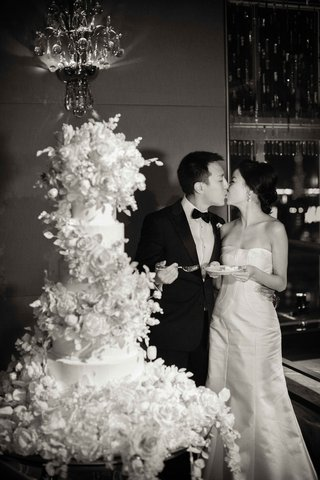 black-and-white-photo-of-bride-in-strapless-wedding-dress-kissing-groom-after-cake-cutting