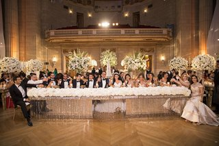 bride-and-groom-with-bridesmaids-and-groomsmen-at-head-table-crystals-flower-runner-ballroom-chevron