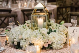 white-lit-candle-in-lantern-with-white-flowers-centerpiece