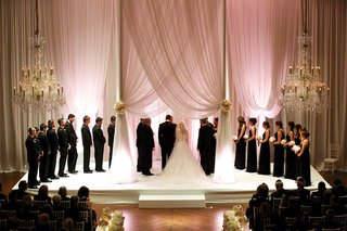 bride-in-vera-wang-wedding-dress-under-draped-chuppah-with-bridesmaids-groomsmen-pink-lighting