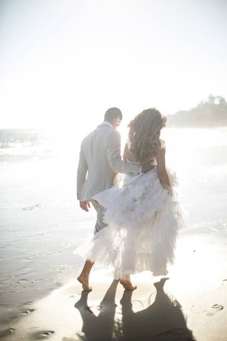 katrina-hodgson-and-brian-scott-walk-on-beach-in-wedding-dress