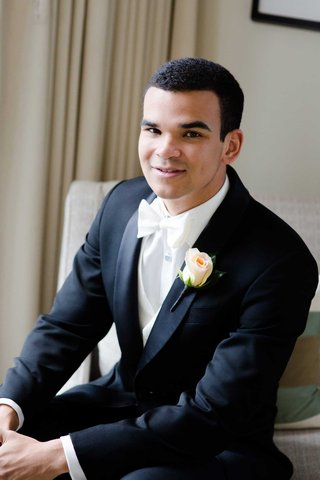 groom-in-nice-black-suit-tuxedo-with-white-bow-tie-and-rose-boutonniere-peach-pink
