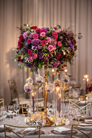 tall-gold-centerpiece-with-pink-purple-burgundy-flowers-greenery-glass-orbs-taper-candles