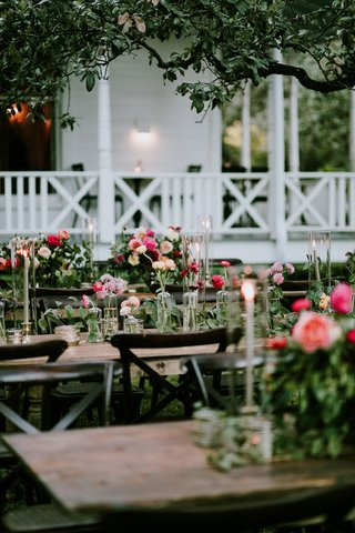 wedding-reception-long-tables-pink-orange-flowers-taper-candles-farmhouse-venue-austin-texas