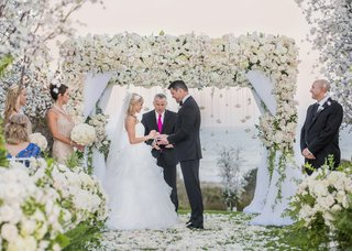 lush-ceremony-arch-with-lots-of-white-flowers-and-drapery