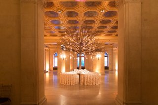 escort-card-table-with-tall-tree-coming-from-round-tables-with-candles-and-flowers
