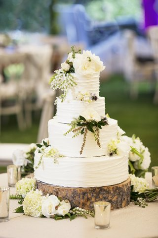 white-round-cake-on-wooden-slice-with-flowers