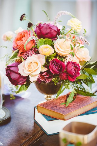 outdoor-bohemian-wedding-reception-table-aged-books-pink-red-peach-flowers-greenery