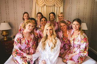 wedding-getting-ready-photo-bride-in-white-robe-bridesmaids-in-pink-flower-print-robes-on-bed