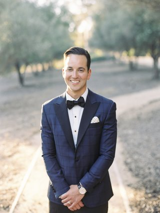 groom-in-blue-windowpane-suit-jacket-with-navy-lapels-and-bow-tie-polka-dot-pocket-square