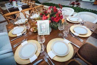 small-square-wooden-table-with-gold-charger-plates-and-small-centerpieces-red-pink-orange-greenery
