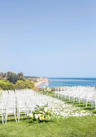 wedding-ceremony-on-grass-bluff-overlooking-pacific-ocean-beach-white-chair-yellow-flowers-sunny