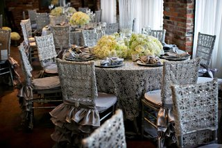 silver-table-linens-and-ruffle-chair-covers-with-low-ivory-flower-centerpieces