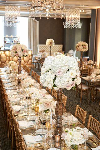 gold-chiavari-chairs-rose-centerpieces-on-long-family-tables-with-mirror-tops-under-chandelier