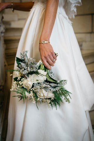 bride-wearing-mothers-wedding-dress-and-holding-winter-wedding-bouquet-white-flowers-greenery