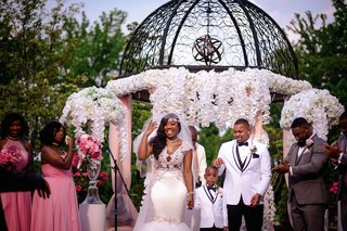 wedding-ceremony-outdoor-bride-and-groom-under-iron-structure-white-orchids-pink-bridesmaids