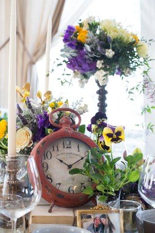 table-decor-clock-purple-yellow-flowers-new-york-city-bridal-shower-pre-wedding-trinkets-photo
