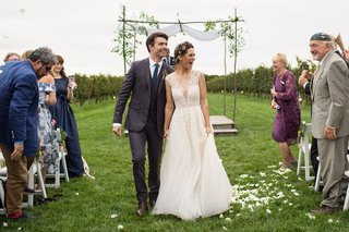 lyndsy-fonseca-and-noah-bean-wedding-walking-up-aisle-in-vineyard-ceremony-guests-and-family-happy