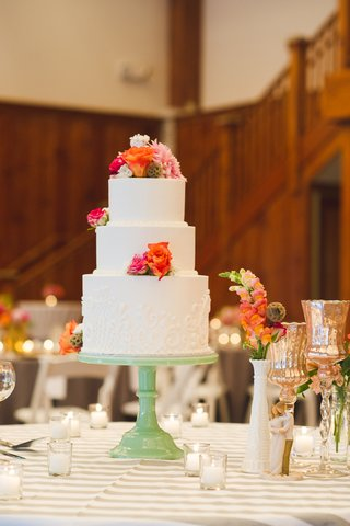 white-cake-with-fresh-flowers-in-peach-and-pink