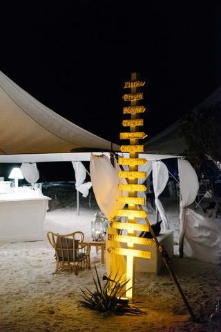 bahamas-destination-wedding-with-directional-wood-sign-arrows-outside-of-tent-on-sand