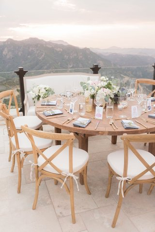 wedding-reception-overlooking-malibu-mountains-canyons-wood-chairs-white-cushions-low-centerpiece