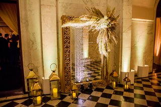 gold-framed-mirror-seating-chart-with-pampas-grass-on-the-corner-lanterns