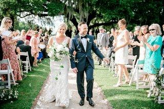 bride-in-wedding-dress-groom-in-blue-tuxedo-guests-on-grass-lawn-south-carolina-destination-wedding