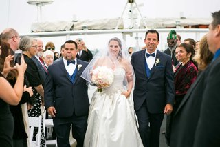 bride-in-allure-ball-gown-walked-down-the-aisle-by-her-dad-and-stepdad